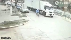 Man rides a bicycle into a truck's blind spot as it makes turn and get wiped