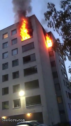 A man jumping from a burning apartment a few stories high