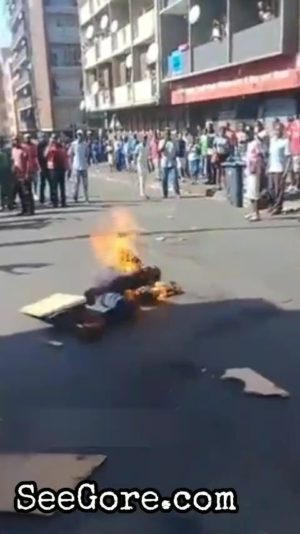 Crowd watches a man being  burned alive